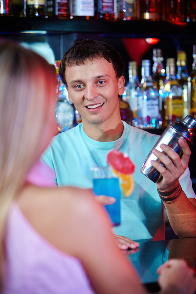 Portrait Of Smiling Male With Bottle Looking At Girl In The Bar