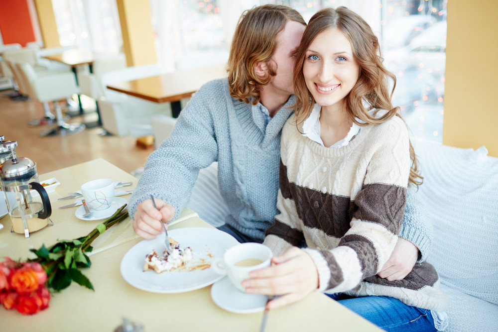Portrait Of Happy Young Female Looking At Camera With Her Boyfriend Near By