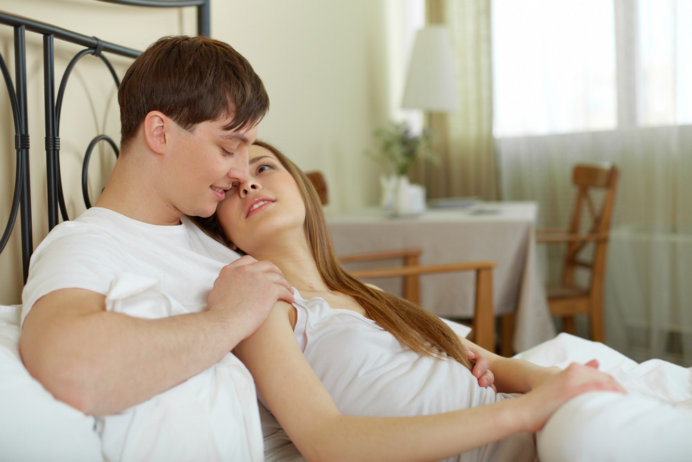 Amorous Couple Lying In Bed And Looking At One Another
