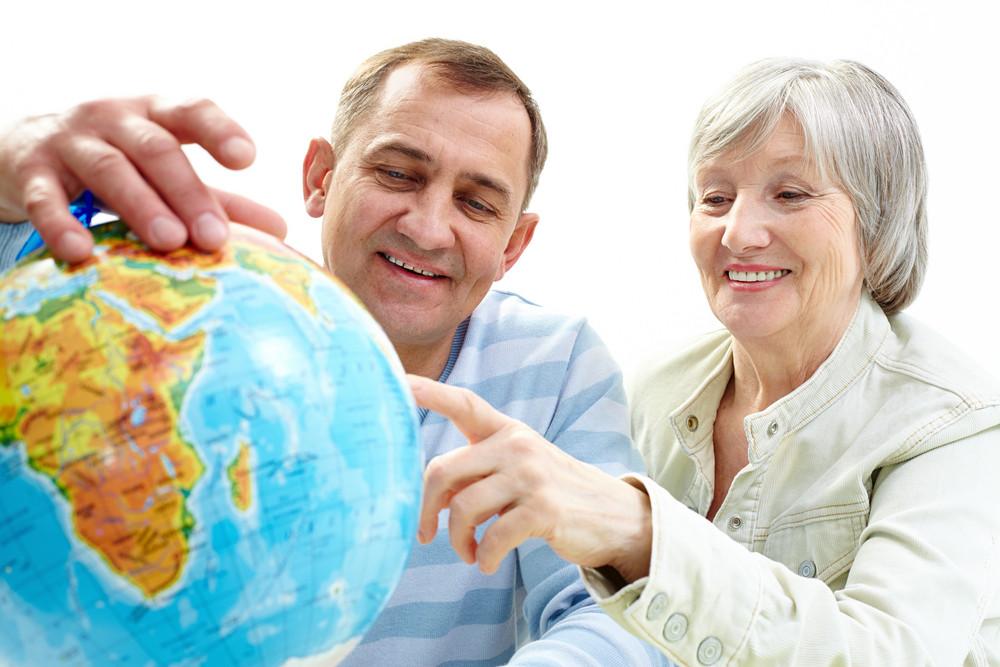 Portrait Of Happy Senior Couple Looking At Globe