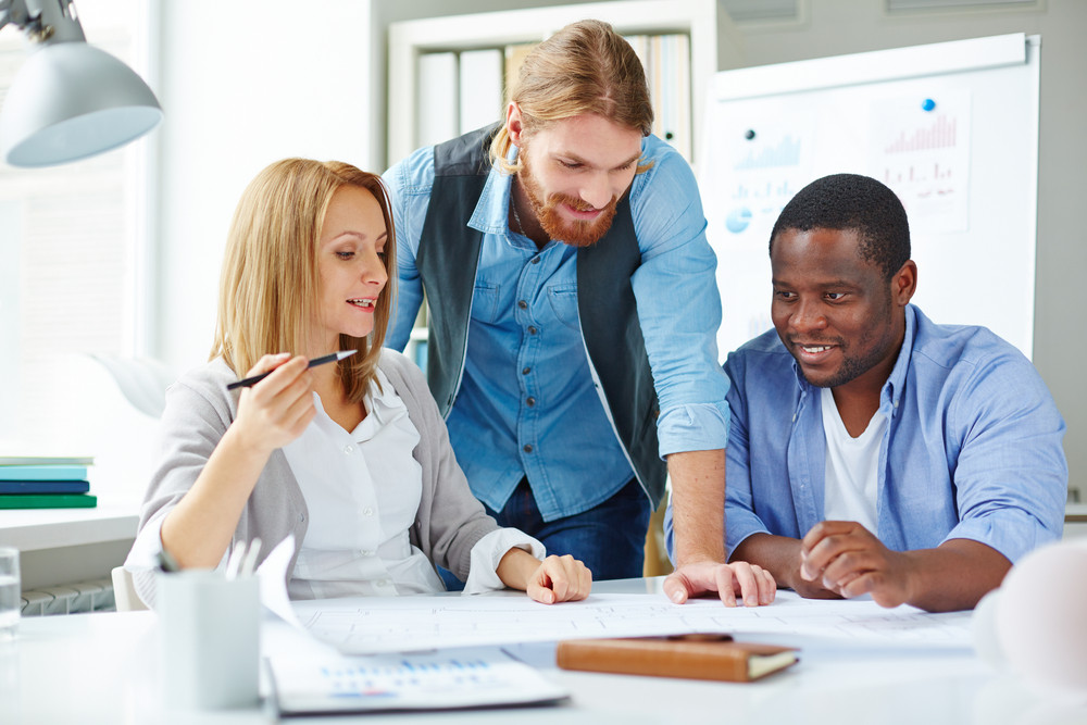 Multi-ethnic Employees Looking At Blueprint While Explaining Its Features