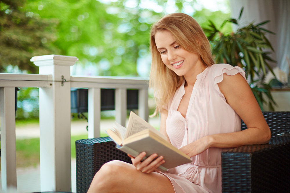 Portrait Of Cute Girl Reading A Book At Leisure