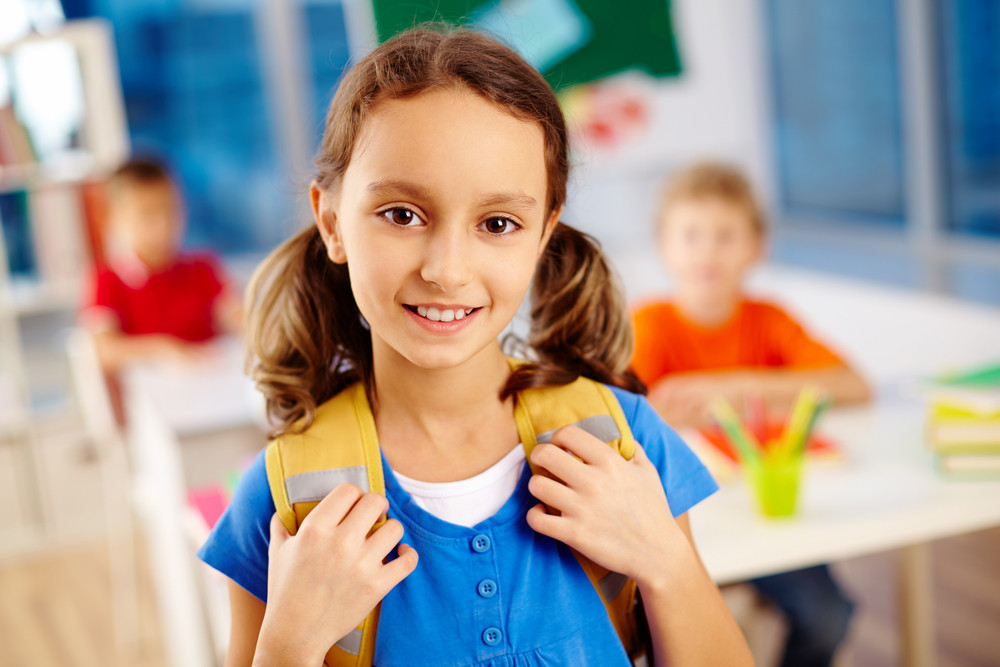 Portrait Of Cute Schoolgirl With Backpack Looking At Camera With Classmates On Background