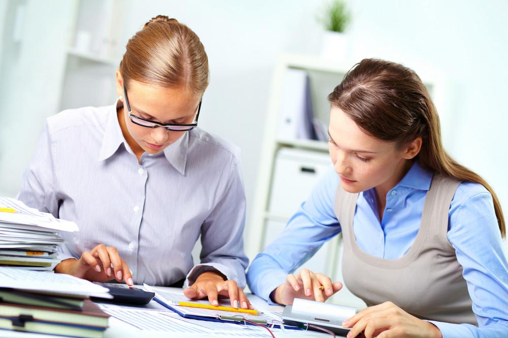 肖像兩位年輕的女企業家工作有了計算器在Office