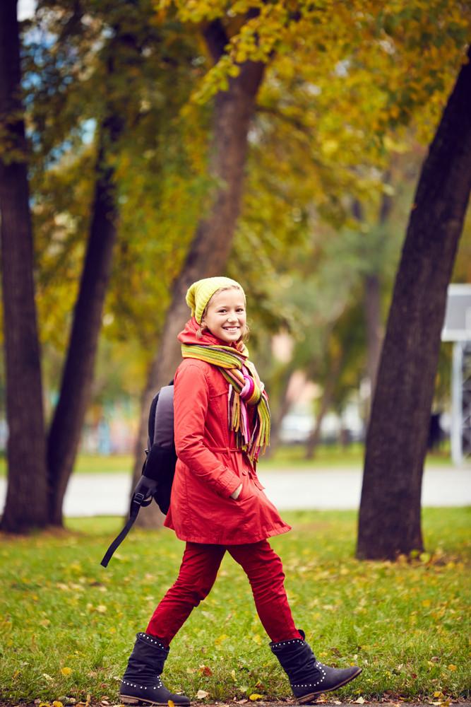 Portrait Of Happy Schoolgirl In Casual Going To School Through Park
