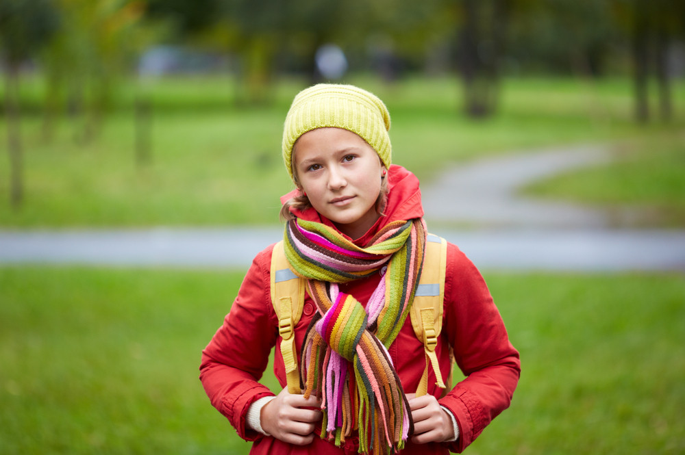 Portrait Of Calm Schoolgirl With Backpack Looking At Camera Outside