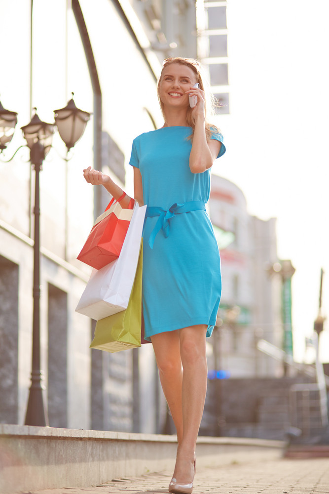 Portrait Of Happy Girl With Shopping Bags Calling Outdoors