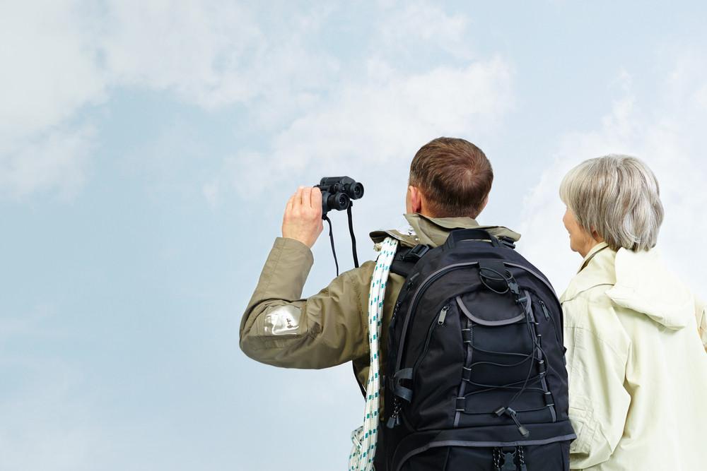 Backs Of Senior Hikers With Binoculars On Trip
