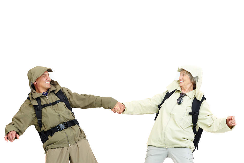 Couple Of Happy Senior Hikers Holding By Hands