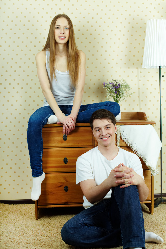 Happy Couple In Casual Clothes Looking At Camera