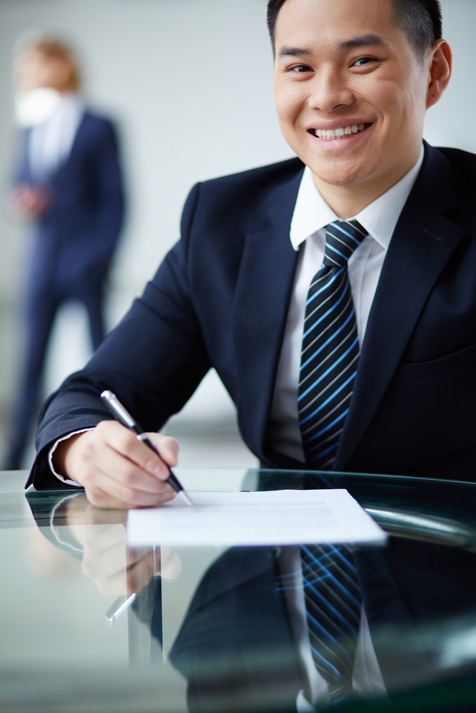 Portrait Of Smiling Businessman Looking At Camera At Workplace