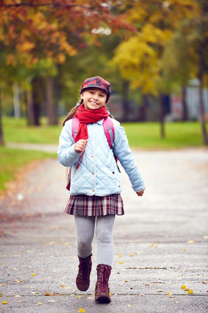 Portrait Of Smiling Schoolgirl With Backpack Going To School