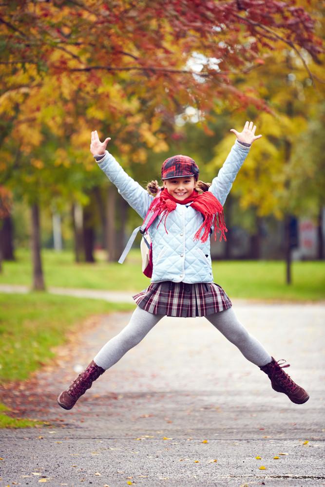 Portrait Of Happy Schoolgirl In Jump Looking At Camera