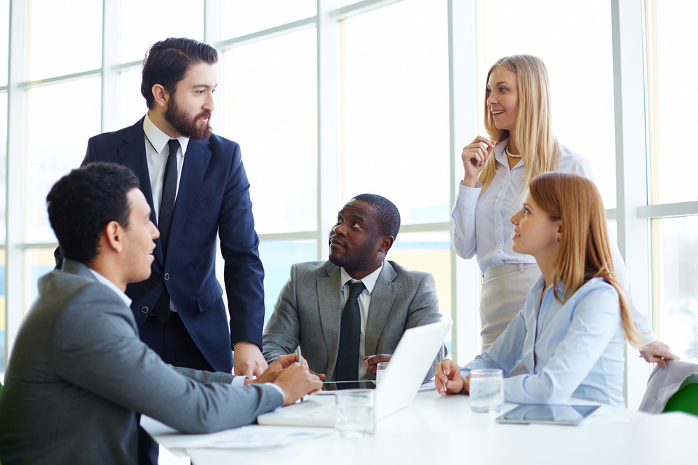Group Of Business Partners Listening To Their Boss At Meeting In Office