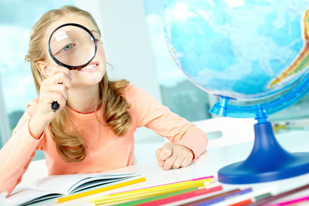 Portrait Of Cute Schoolgirl Looking At Globe Through Spy Glass