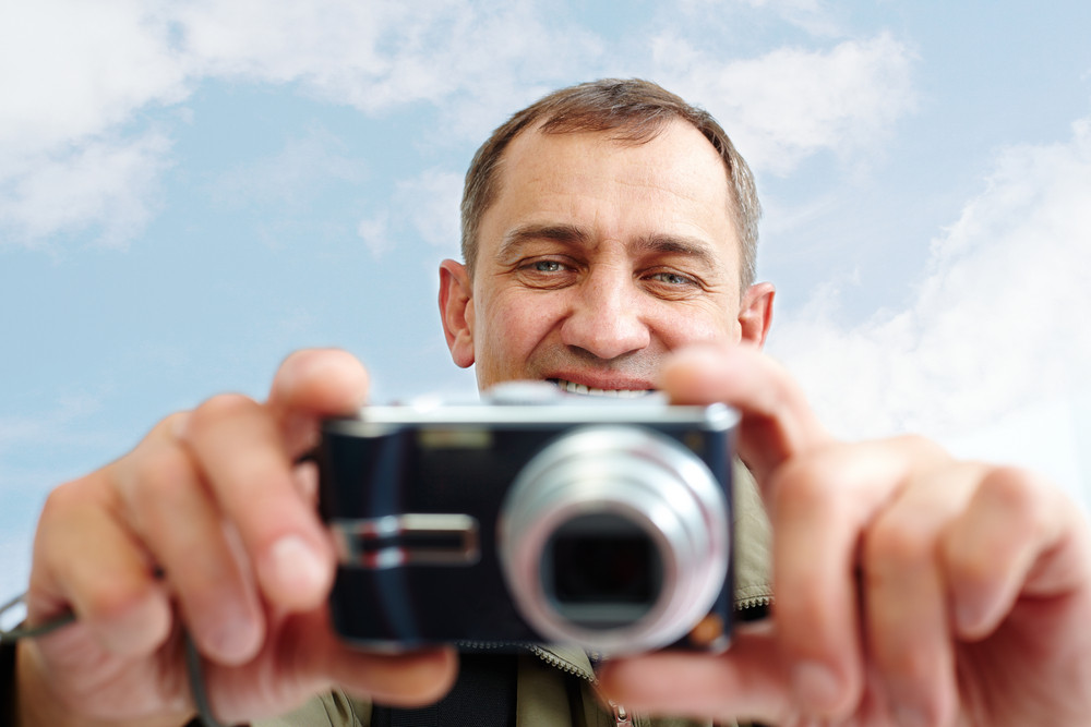 Portrait Of Mature Man Taking Pictures Against Cloudy Sky