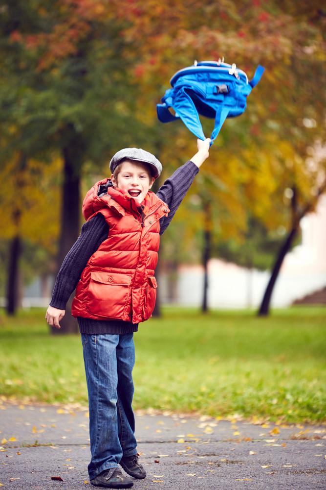 Portrait Of Joyful Schoolboy With Backpack Having Fun In Park