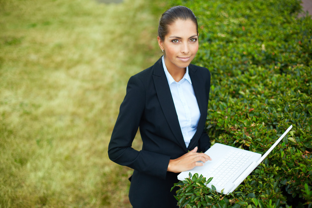 Image Of Young Businesswoman With Laptop Looking At Camera While Networking In Park