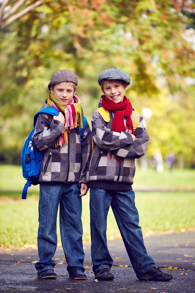 Portrait Of Happy Schoolboys In Casual Looking At Camera In Park