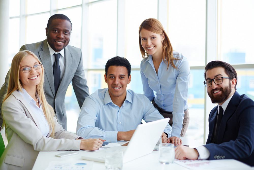 Company Of Five Employees Sitting At Workplace In Office