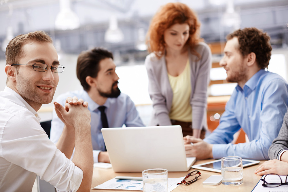 Attractive Businessman Looking At Camera On Background Of Partners Discussing Ideas