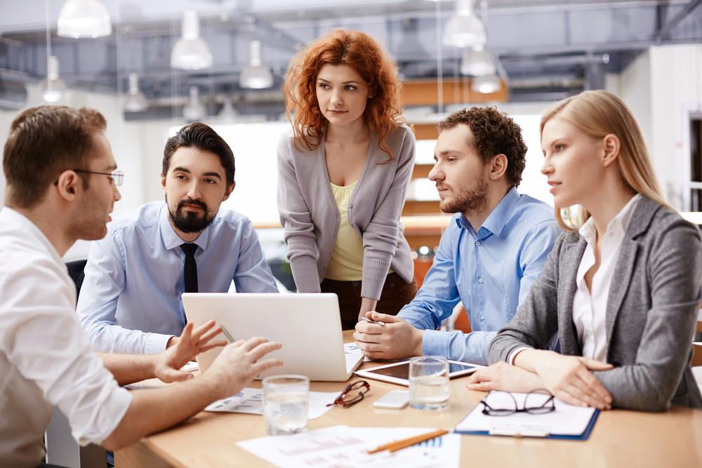 Group Of Business Partners Listening To Colleague At Meeting