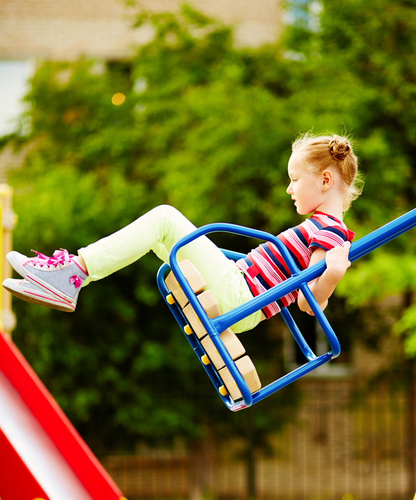 Portrait Of Little Girl Swinging On Playground Area