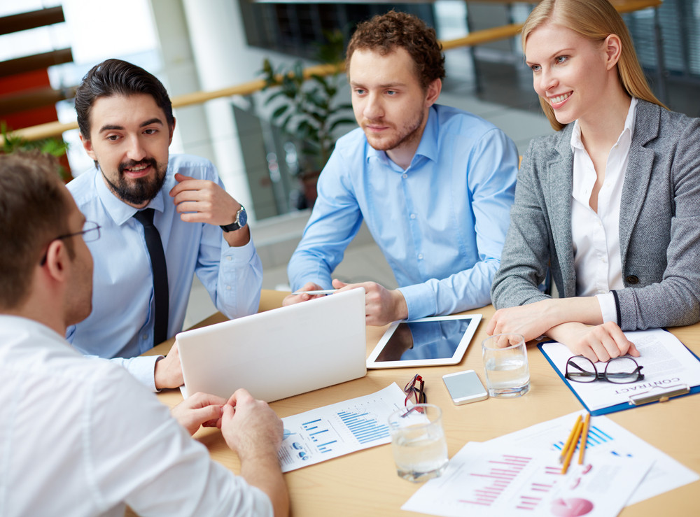 Group Of Business Partners Interviewing Young Man At Meeting