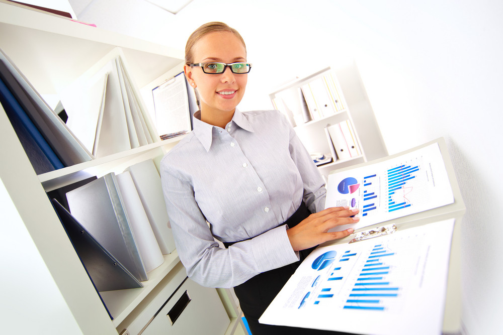 Portrait Of Elegant Businesswoman With Papers Looking At Camera In Office