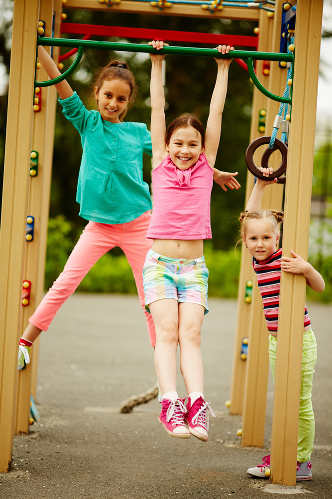 Happy Little Girls Looking At Camera On Playground Area