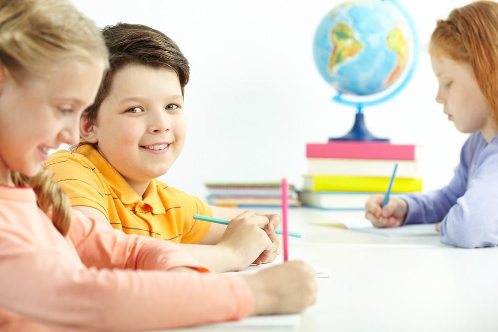 Portrait Of Happy Schoolboy Looking At Camera Between Two Girls
