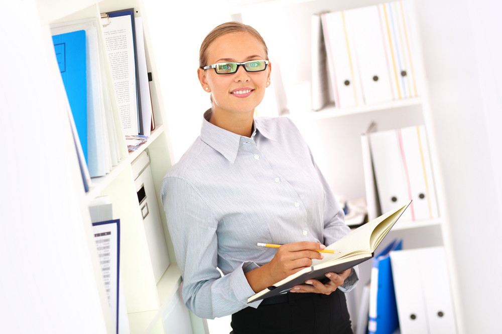 Portrait Of A Smiling Bookkeeper Standing By The Shelves