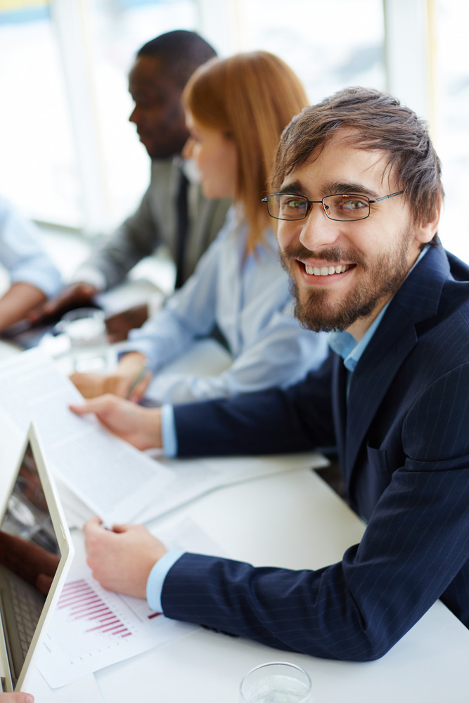 Young Businessman Looking At Camera At Meeting With Group Of Partners On Background