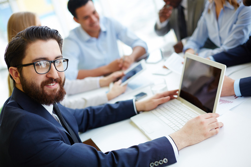 Bearded Businessman Looking At Camera At Meeting With Group Of Partners Interacting On Background