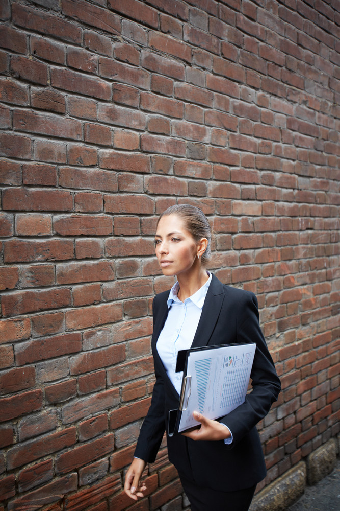 Image Of Confident Businesswoman With Document Walking Along Brick Wall