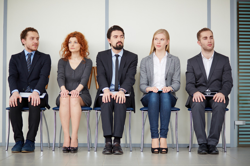 Portrait Of Several Elegant Employees Sitting On Chairs