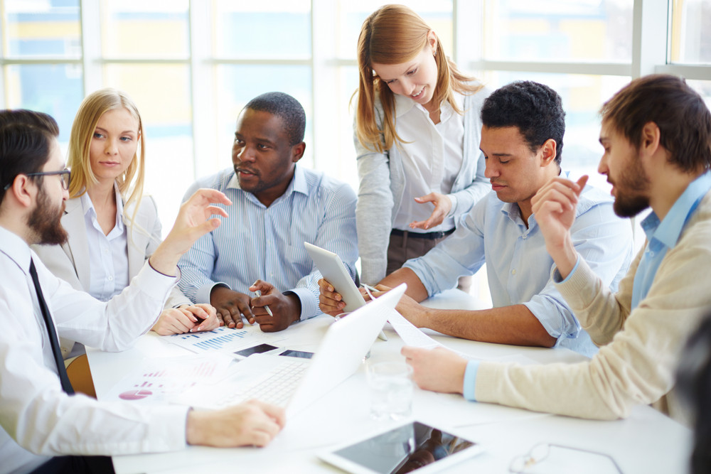 Group Of Confident Business Partners Interacting At Meeting