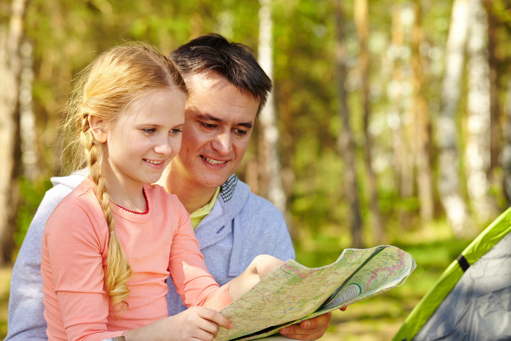 Portrait Of Father And His Daughter Looking At Map While On Trip