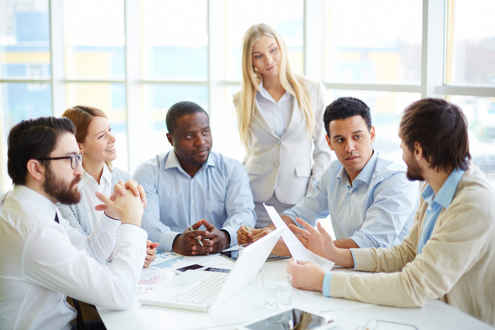Group Of Business Partners Listening To One Of Colleagues At Meeting