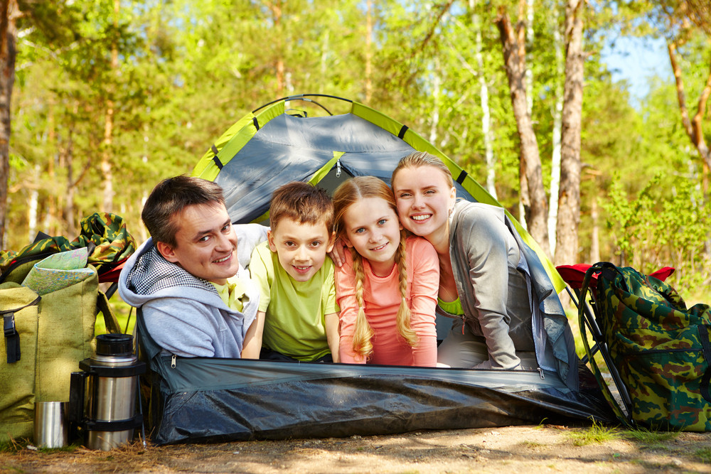 Portrait Of Family Of Travelers In Tent Looking At Camera