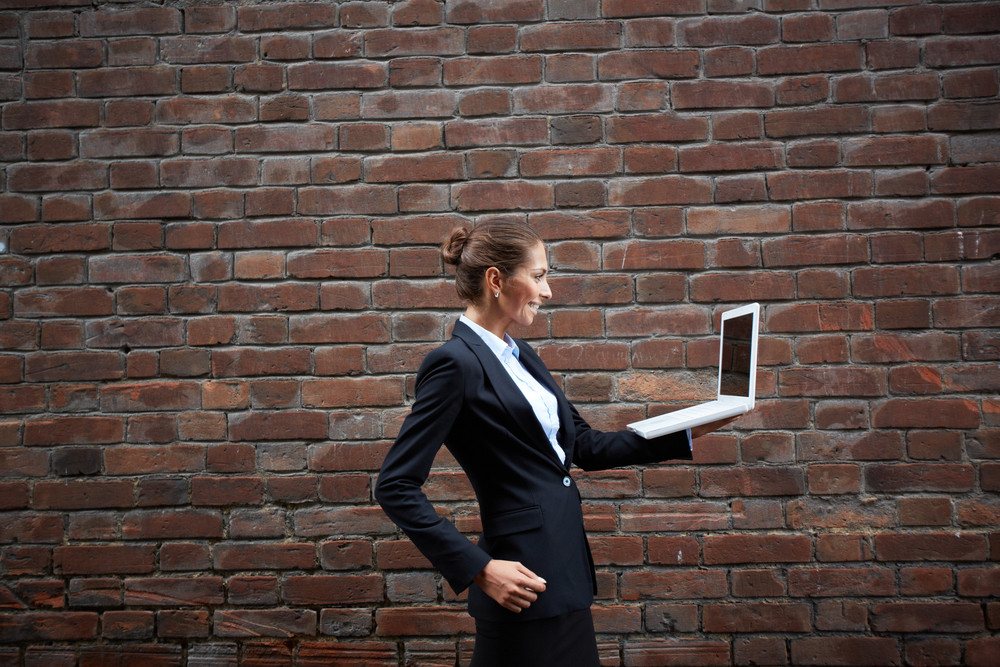 Image Of Smiling Businesswoman With Laptop Walking Along Brick Wall