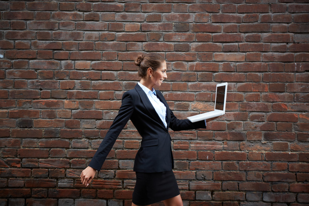 Image Of Elegant Businesswoman With Laptop Walking Along Brick Wall