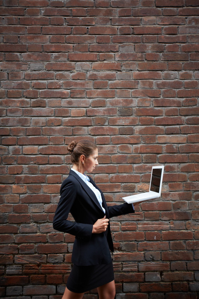 Image Of Confident Businesswoman With Laptop Walking Along Brick Wall