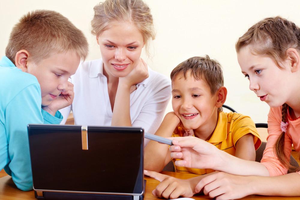 Smart Schoolchildren And Teacher Working With Netbook In Class