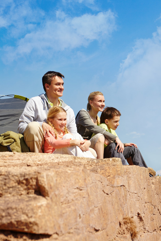 Portrait Of Family Of Travelers Sitting On Rocky Cliff