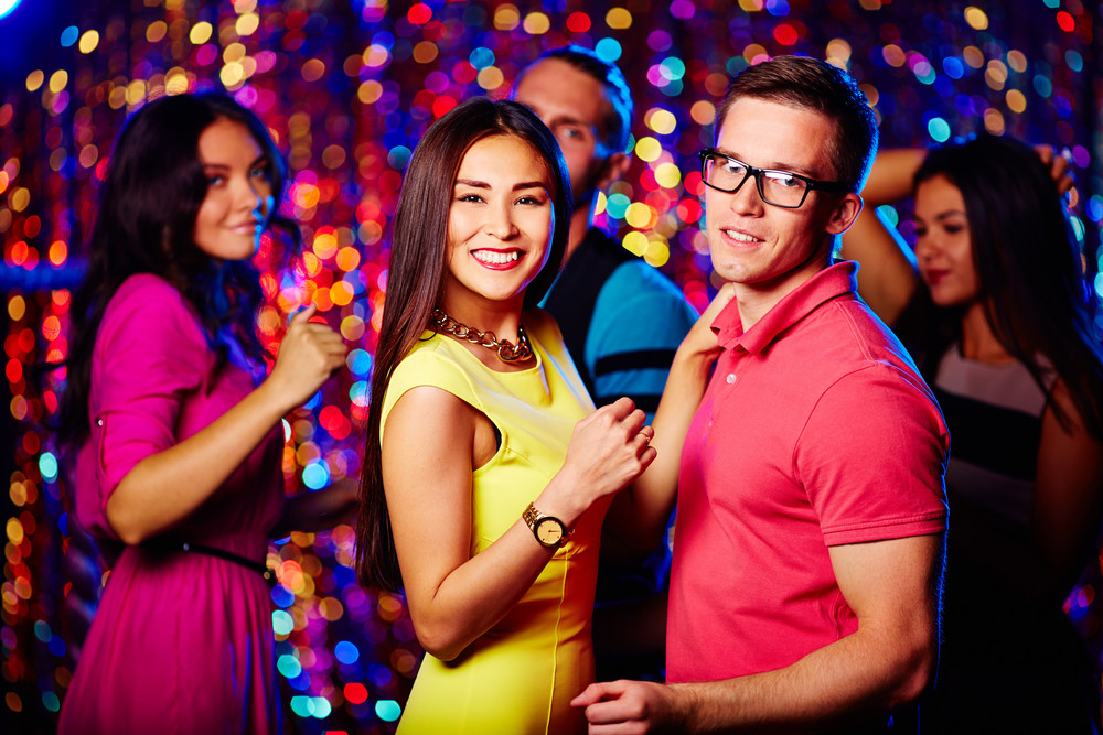 Young Couple Dancing At Nightclub On Background Of Their Friends