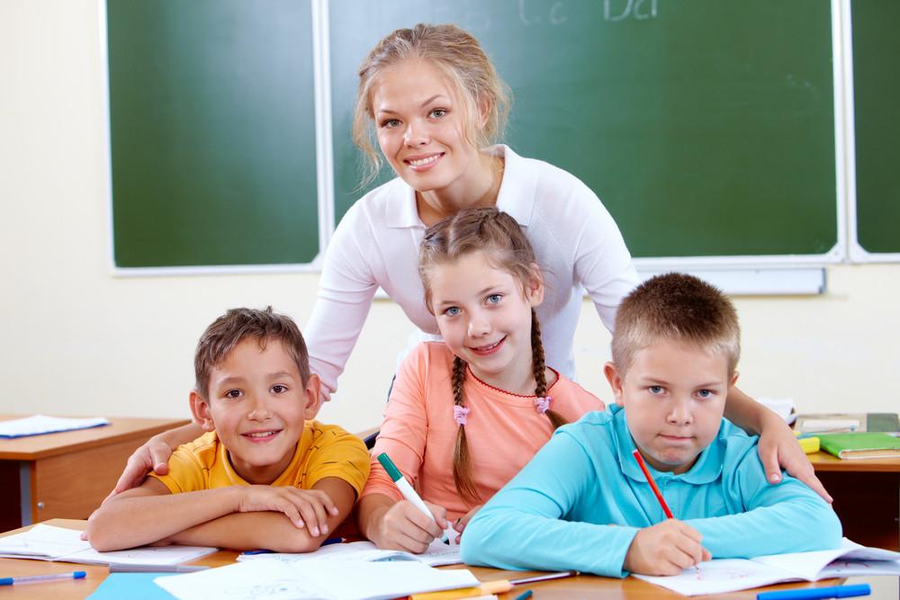 Portrait Of Cute Schoolchildren And Teacher In Classroom