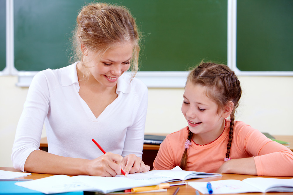 Portrait Of Young Teacher Showing Her Pupil How To Draw At Lesson