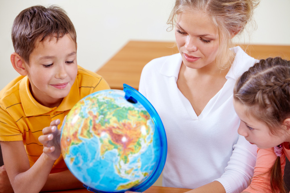 Portrait Of Cute Classmates And Teacher Looking At Globe At Geography Lesson