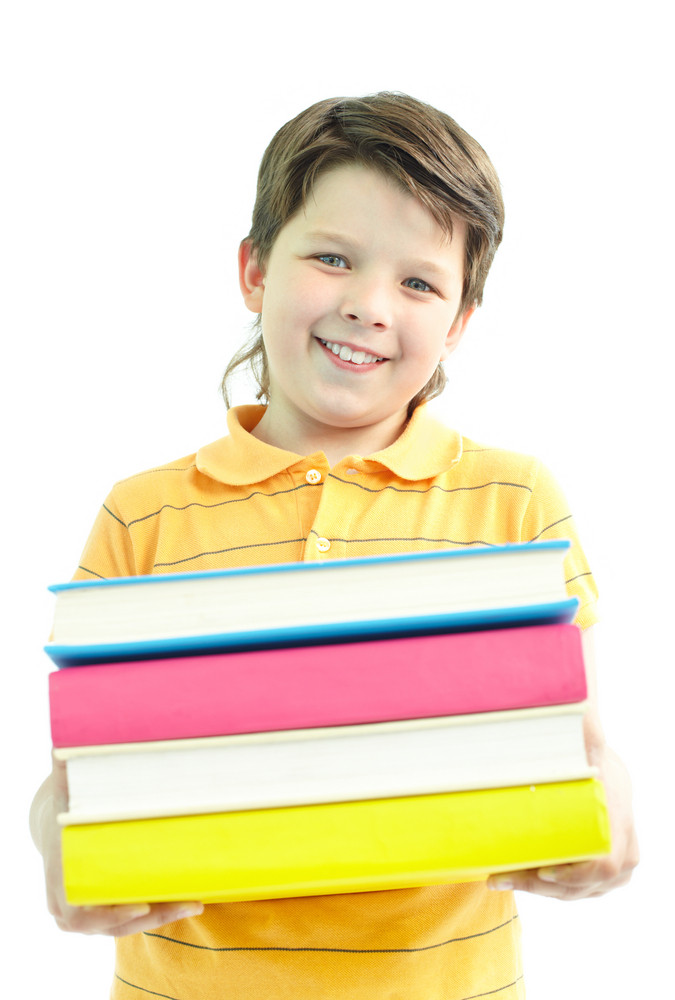 Portrait Of Happy Boy With Stack Of Books Looking At Camera